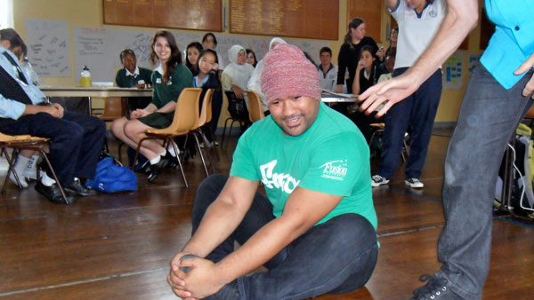 Youth worker sitting on the floor performing an ice breaker exercise during a youth forum